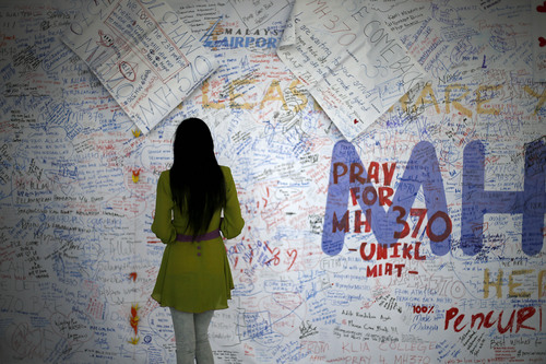 A woman reads messages and well wishes to people involved with the missing Malaysia Airlines jetliner MH370, Saturday, March 15, 2014 in Sepang, Malaysia. A Malaysian passenger jet missing for more than a week had its communications deliberately disabled and its last signal came about seven and a half hours after takeoff, meaning it could have ended up as far as Kazakhstan or deep in the southern Indian Ocean, Malaysia's Prime Minister Najib Razak said Saturday. (AP Photo/Wong Maye-E)