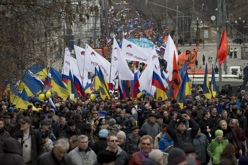 Demonstrators carrying Russian and Ukrainian flags march to oppose  president Vladimir Putin's policies in Ukraine, in Moscow, Saturday, March 15, 2014. Large rival marches have taken place in Moscow over Kremlin-backed plans for Ukraine's province of Crimea to break away and merge with Russia. More than 10,000 people turned out Saturday for a rally in the center of the city held to oppose what many demonstrators described as Russia's invasion of the Crimean Peninsula. In a nearby location, a similar sized crowd voiced its support for Crimea's ethnic Russian majority, who Moscow insists is at threat from an aggressively nationalist leadership now running Ukraine. (AP Photo/Alexander Zemlianichenko)