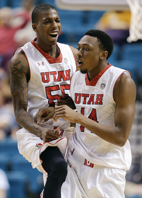 Utah's Delon Wright, left, congratulates Dakarai Tucker after Tucker made a three-point shot to break a tie late in an NCAA Pac 12 conference tournament college basketball game against Washington, Wednesday, March 12, 2014, in Las Vegas. Utah won 67-61. (AP Photo/Julie Jacobson)