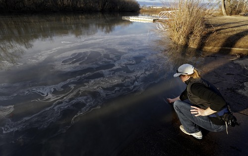 FILE - In this Wednesday, Feb. 5, 2014 file photo, Amy Adams, North Carolina campaign coordinator with Appalachian Voices dips her hand into the Dan River in Danville, Va. as signs of coal ash appear in the river. Documents and interviews collected by The Associated Press show how Duke's lobbyists prodded Republican legislators to tuck a 330-word provision in a regulatory reform bill running nearly 60 single-spaced pages. Though the bill never once mentions coal ash, the change allowed Duke to avoid any costly cleanup of contaminated groundwater leaching from its unlined dumps toward rivers, lakes and the drinking wells of nearby homeowners. (AP Photo/Gerry Broome, File)