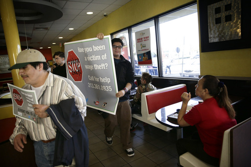 Demonstrators carry banners and signs as they march inside a McDonald's restaurant to protest for higher wages on Tuesday, March 18, 2014, in Huntington Park, Calif. Protesters were set to rally outside McDonald's restaurants in cities including Boston, Chicago and Miami to call attention to the denial of overtime pay and other violations they say deprive workers of the money they're owed. (AP Photo/Jae C. Hong)