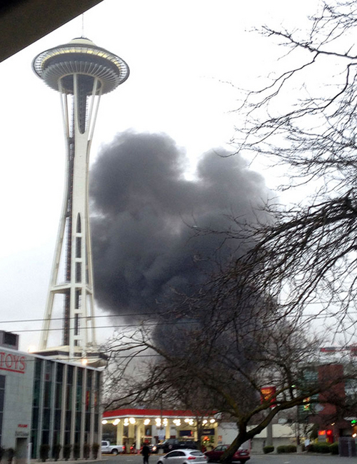 In this photo provided by KIRO- TV,  smoke rises at the scene of a helicopter crash outside the KOMO-TV studios near the space needle in Seattle on Tuesday, March 18, 2014. The station says the helicopter was apparently lifting off Tuesday morning when it possibly hit the side of the building and went down, hitting several vehicles on Broad Street.  (AP Photo/KIRO-TV)