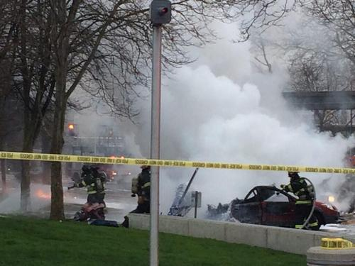 In this photo provided by KOMO-TV, emergency personnel respond to the scene of a helicopter crash outside the KOMO-TV studios near the space needle in Seattle on Tuesday, March 18, 2014. The station says the helicopter was apparently lifting off Tuesday morning when it possibly hit the side of the building and went down, hitting several vehicles on Broad Street.  (AP Photo/KOMO-TV, Kelly Koopmans)