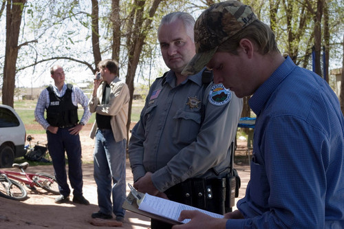 Patrick Pipkin reviews a police report concerning the FLDS's attempted eviction of Pipkin from his home, before filing it with Officer Helaman Barlow of the Colorado City Police Department while Daniel Chatwin talks to Officer Preston Barlow in the background.
