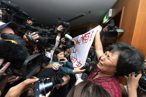 """A Chinese relative of passengers aboard a missing Malaysia Airlines plane cries as she holds a banner in front of journalists reading 'We are against the Malaysian government for hiding the truth and delaying the rescue. Release our families unconditionally!""""  at a hotel in Sepang, Malaysia, Wednesday, March 19, 2014. Malaysian authorities examined new radar data from Thailand that could potentially give clues on how to retrace the course of the Malaysia Airlines plane that vanished early March 8 with 239 people aboard en route from Kuala Lumpur to Beijing. Twenty-six countries are looking for the aircraft as relatives anxiously await news. (AP Photo) MALAYSIA OUT"""
