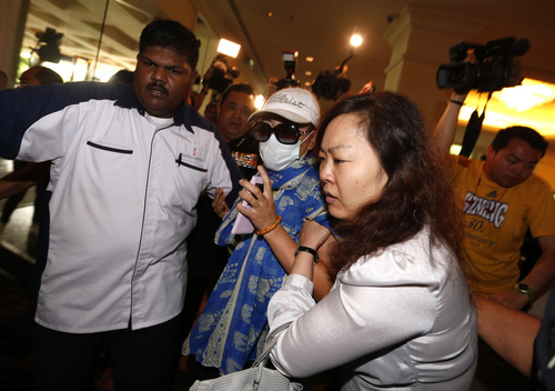 A woman, center,  is carried out by security officials after she tried to protest before a press conference regarding a missing Malaysia Airlines plane at a hotel in Sepang, Malaysia, Wednesday, March 19, 2014. New radar data from Thailand gave Malaysian investigators more potential clues Wednesday for how to retrace the course of the missing Malaysian airliner, while a massive multinational search unfolded in an area the size of Australia. (AP Photo/Vincent Thian)