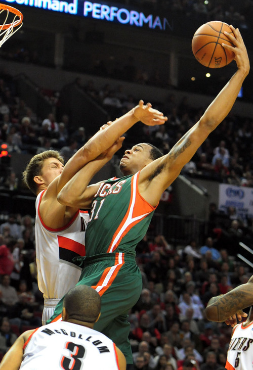 Milwaukee Bucks center John Henson (31) drives to the basket on Portland Trail Blazers center Meyers Leonard (11) during the first half of an NBA basketball game in Portland, Ore., Tuesday, March 18, 2014. (AP Photo/Steve Dykes)