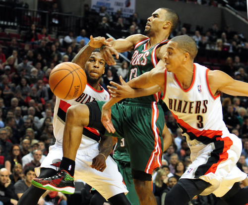 Milwaukee Bucks guard Ramon Sessions (13) has the ball knocked away by Portland Trail Blazers forward Thomas Robinson (41) and guard C.J. McCollum (3) during the first half of an NBA basketball game in Portland, Ore., Tuesday, March 18, 2014. (AP Photo/Steve Dykes)