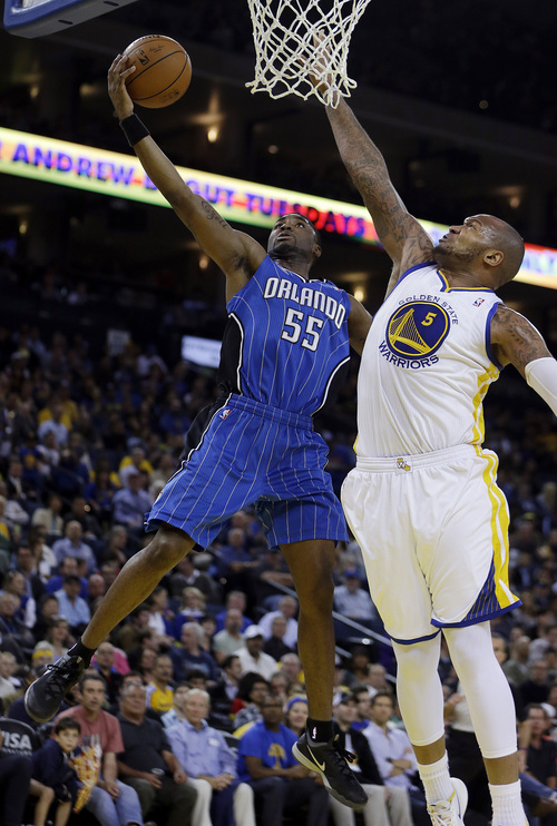 Orlando Magic guard E'Twaun Moore, left, lays up a shot against Golden State Warriors' Marreese Speights (5) during the first half of an NBA basketball game Tuesday, March 18, 2014, in Oakland, Calif. (AP Photo/Ben Margot)