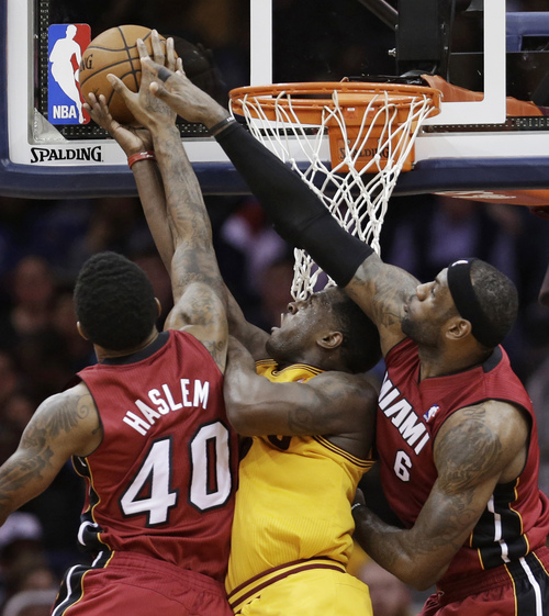 Miami Heat's Udonis Haslem, left, and LeBron James, right, block a shot by Cleveland Cavaliers' Dion Waiters, center, during the fourth quarter of an NBA basketball game Tuesday, March 18, 2014, in Cleveland.  Miami defeated Cleveland 100-96. (AP Photo/Tony Dejak)