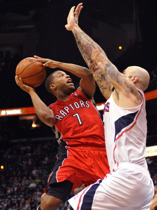 Toronto Raptors' Kyle Lowry (7) is blocked by Atlanta Hawks' Pero Antic (6) in the second half of their NBA basketball game Tuesday, March 18, 2014, in Atlanta. Atlanta won 118-113 in overtime. (AP Photo/David Tulis)