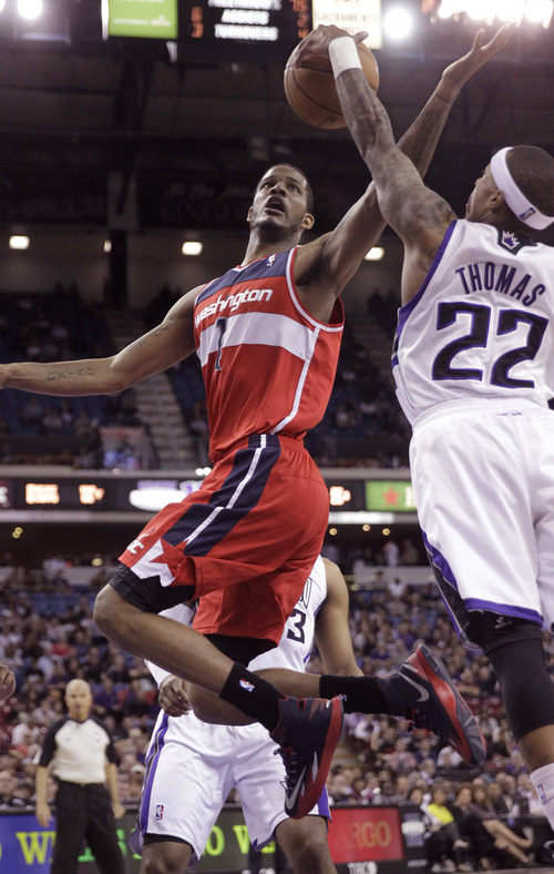 Washington Wizards forward Trevor Ariza, left, has his shot blocked by Sacramento Kings guard Isaiah Thomas during the first quarter of an NBA basketball game in Sacramento, Calif., Tuesday, March 18, 2014.(AP Photo/Rich Pedroncelli)