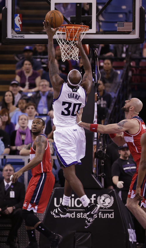 Sacramento Kings forward Reggie Evans, center, goes to the basket between Washington Wizards' Trevor Booker, left, and Marcin Gortat, of Poland during the first quarter of an NBA basketball game in Sacramento, Calif., Tuesday, March 18, 2014.(AP Photo/Rich Pedroncelli)