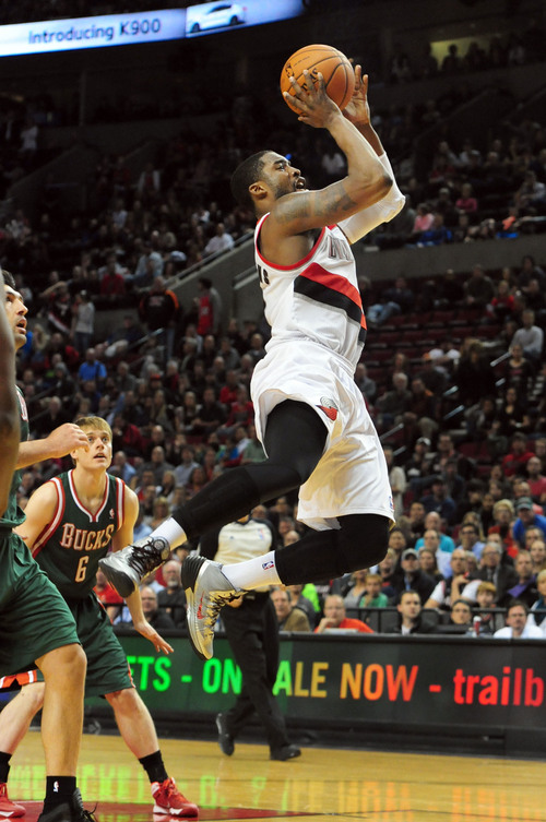 Portland Trail Blazers guard Wesley Matthews (2) hits a shot as Milwaukee Bucks guard Nate Wolters (6) looks on during overtime of an NBA basketball game in Portland, Ore., Tuesday, March 18, 2014. The Blazers won the game 120-115 in overtime. (AP Photo/Steve Dykes)