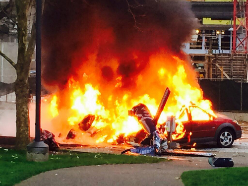 In this photo provided by KOMO-TV, a car burns at the scene of a news helicopter crash outside the KOMO-TV studios near the space needle in Seattle on Tuesday, March 18, 2014. The chopper was taking off from a helipad on KOMO-TV's roof when it went down at a busy downtown intersection and hit three vehicles, starting them on fire and spewing burning fuel down the street. Two people on board the helicopter died. (AP Photo/KOMO-TV, Kelly Koopmans) MANDATORY CREDIT: KOMO-TV