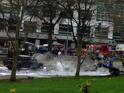 Emergency personnel respond to the scene of a helicopter crash outside the KOMO-TV studios near the space needle in Seattle on Tuesday, March 18, 2014. The chopper was taking off from a helipad on KOMO-TV's roof when it went down at a busy downtown intersection and hit three vehicles, starting them on fire and spewing burning fuel down the street. Two people on board the helicopter died. (AP Photo/The Seattle Times, Mike Siegel)  SEATTLE OUT; USA TODAY OUT; MAGS OUT; TELEVISION OUT; NO SALES; MANDATORY CREDIT TO BOTH THE SEATTLE TIMES AND THE PHOTOGRAPHER