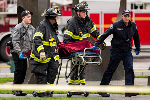 Emergency personnel wheel away one of two bodies from the aftermath of a news helicopter crash Tuesday, March 18, 2014, in Seattle, Wash. A KOMO-TV helicopter crashed into a city street near Seattle's Space Needle, killing two people and critically injuring a person in a car on the ground. (AP Photo/seattlepi.com, Jordan Stead) MAGS OUT; NO SALES; SEATTLE TIMES OUT; MANDATORY CREDIT; TV OUT