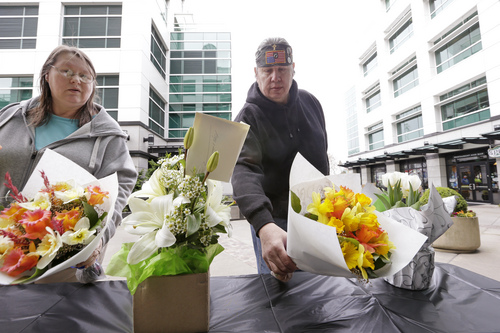 Cindy Quiring, left, and her husband Roger place flowers at a memorial outside Fisher Plaza, home to KOMO-TV, following a helicopter crash outside the building earlier Tuesday, March 18, 2014, in Seattle. The news helicopter crashed into a city street near Seattle's Space Needle, killing two people and critically injuring a person in a car on the ground.  (AP Photo/Elaine Thompson)