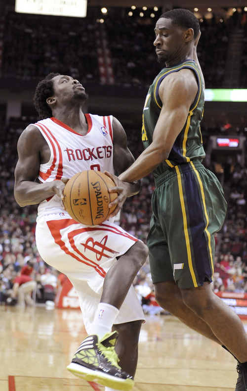 Houston Rockets's Patrick Beverley, left, goes up against Utah Jazz's Ian Clark in the first half of an NBA basketball game Monday, March 17, 2014, in Houston. (AP Photo/Pat Sullivan)