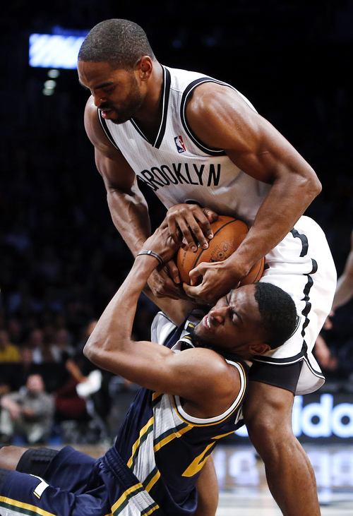 Brooklyn Nets' Alan Anderson, above, tries to rip the ball away from Utah Jazz's Ian Clark during the second half of an NBA basketball game Tuesday, Nov. 5, 2013, in New York. Brooklyn defeated Utah 104-88. (AP Photo/Jason DeCrow)