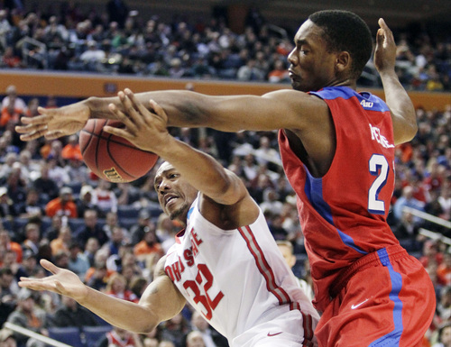 Dayton's Dyshawn Pierre (21) knocks the ball away from Ohio State's Lenzelle Smith Jr. (32) during the first half of a second-round game in the NCAA college basketball tournament in Buffalo, N.Y., Thursday, March 20, 2014. (AP Photo/Bill Wippert)