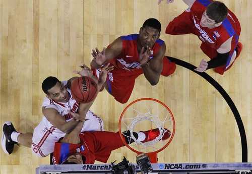 Ohio State's LaQuinton Ross, left, battles for the ball with Dayton's Devin Oliver, Dyshawn Pierre, center, and Matt Kavanaugh, right, during the first half of a second-round game in the NCAA college basketball tournament in Buffalo, N.Y., Thursday, March 20, 2014. (AP Photo/Bill Wippert)