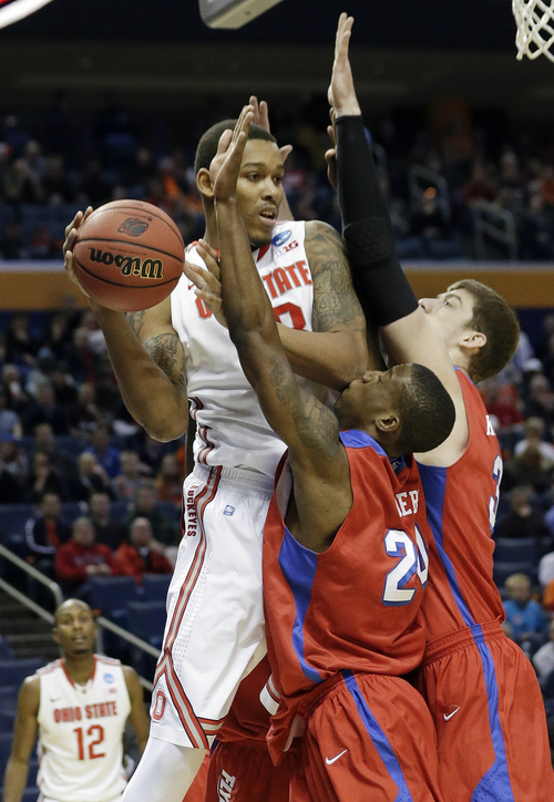 Ohio State's Amir Williams, left, passes away from Dayton's Jordan Sibert (24) and Matt Kavanaugh, right, during the first half of a second-round game in the NCAA college basketball tournament in Buffalo, N.Y., Thursday, March 20, 2014. (AP Photo/Frank Franklin II)