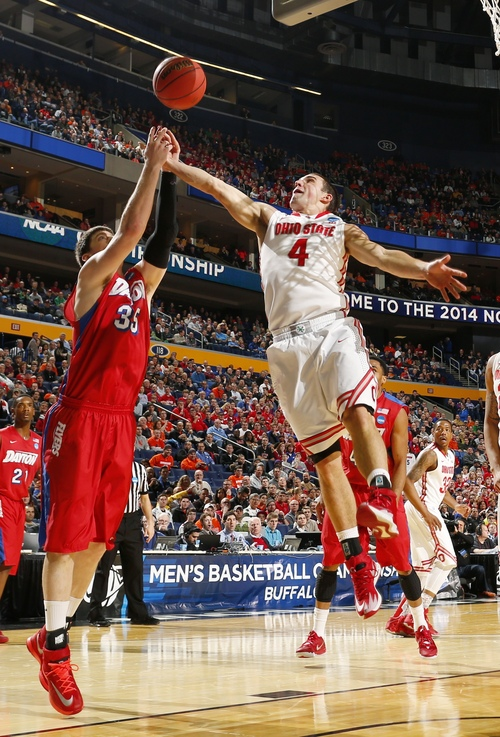 Ohio State's Aaron Craft (4) fights for control of the ball with Dayton's Matt Kavanaugh (35) during the first half of a second-round game in the NCAA college basketball tournament in Buffalo, N.Y., Thursday, March 20, 2014. (AP Photo/Bill Wippert)