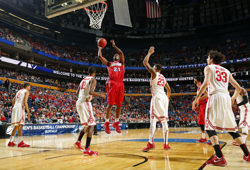 Dayton's Dyshawn Pierre (21) shoots the ball over Ohio State's Sam Thompson (12) during the first half of a second-round game in the NCAA college basketball tournament in Buffalo, N.Y., Thursday, March 20, 2014. (AP Photo/Bill Wippert)