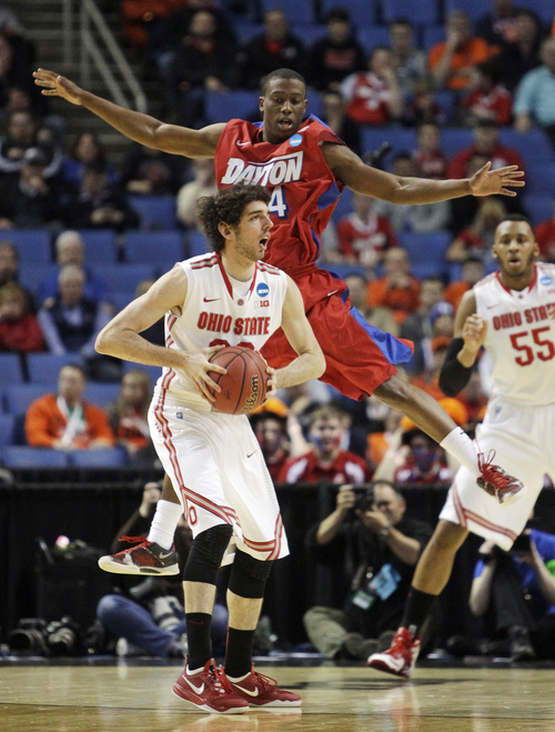Ohio State's Amedeo Della Valle, front, passes away from Dayton's Jordan Sibert during the first half of a second-round game in the NCAA college basketball tournament in Buffalo, N.Y., Thursday, March 20, 2014. (AP Photo/Bill Wippert)
