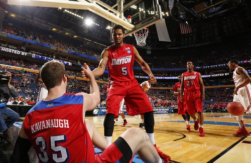 Dayton's Devin Oliver (5) helps up teammate Matt Kavanaugh (35) after he fell on a play during the first half of a second-round game in the NCAA college basketball tournament against Ohio State in Buffalo, N.Y., Thursday, March 20, 2014. (AP Photo/Bill Wippert)