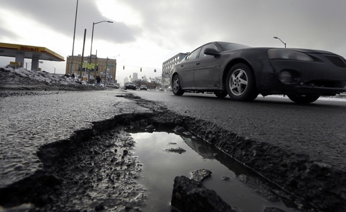FILE - In this Feb. 11, 2014 file photo a car drives by a pothole in Detroit. As spring officially begins Thursday, officials across much of the nation are still paying the bills for keeping roads clear during the cold, snowy winter. The state expects to spend as much as $140 million for winter maintenance after budgeting just $88 million. (AP Photo/Carlos Osorio, File)