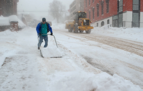 In this Feb. 22, 2014 photo a man clears a sidewalk as city crews use heavy equipment to clear roads in downtown Houghton, Mich. In a part of the state where 200 inches of snow in a single season elicits barely a shrug, officials know there's nothing in the budget more important than keeping the roads passable. Houghton County planned to spend around $2.1 million for plowing, salting and related maintenance, which experience suggested would be plenty, but has overshot it by $500,000 and counting. (AP Photo/The Daily Mining Gazette, Kurt Hauglie)