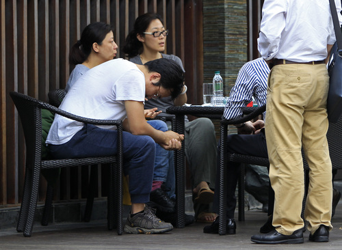 A Chinese relative, in a T-shirt, of passengers aboard a missing Malaysia Airlines plane, looks down as he sits outside a cafe at a resort in Cyberjaya, Malaysia, Thursday, March 20, 2014. Flight 370 disappeared March 8 on a night flight from Kuala Lumpur to Beijing. Malaysian authorities have not ruled out any possible explanation, but have said the evidence so far suggests the flight was deliberately turned back across Malaysia to the Strait of Malacca, with its communications systems disabled. (AP Photo/Lai Seng Sin)