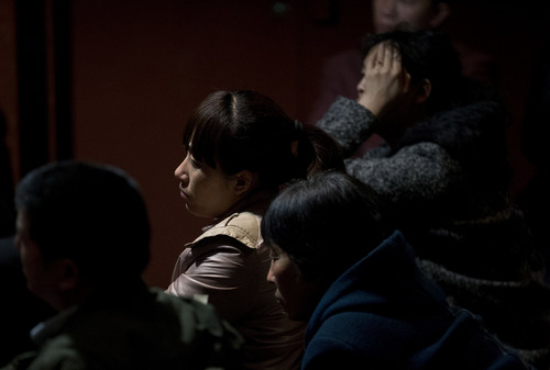 Relatives of Chinese passengers aboard the missing Malaysia Airlines, MH370 watch a TV news program about the plane at a hotel ballroom in Beijing, China, Thursday, March 20, 2014. Four military search planes were dispatched Thursday to try to determine whether two large objects bobbing in a remote part of the Indian Ocean spotted by satellite imagery were part of a possible debris field of the missing Malaysia Airlines flight. (AP Photo/Andy Wong)