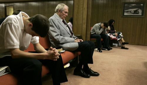 In this March 19, 2006 file photo, the Rev. Fred Phelps Sr., center, sits in prayer at his Westboro Baptist Church in Topeka, Kan. Phelps, the founder of the Kansas church known for anti-gay protests and pickets at military funerals, died late Wednesday, March 19, 2014, his family said. He was 84. (AP Photo/Charlie Riedel, File)
