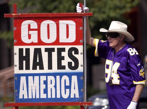 File  |  The Associated Press Fred Phelps Sr., shown displaying one of his many infamous protest signs,  drew international condemnation for outrageous and hate-filled protests that blamed almost everything, including the deaths of AIDS victims and U.S. soldiers, on America's tolerance for gay people.