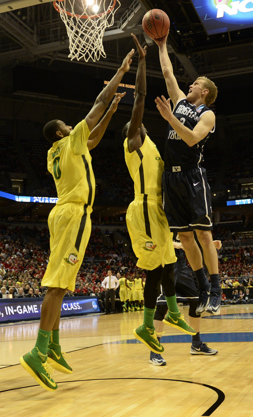 Rick Egan  | The Salt Lake Tribune   Brigham Young Cougars guard Tyler Haws (3) goes up for a shot, as he is double-teamed by the Ducks, in second round NCAA Championship action, BYU vs. Oregon, in Milwaukee, Thursday, March 20, 2014.