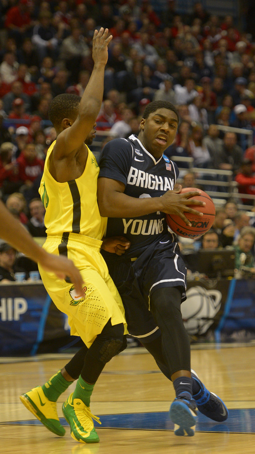 Rick Egan  | The Salt Lake Tribune   Brigham Young Cougars guard Frank Bartley IV (24) takes the ball inside as Oregon Ducks guard Jason Calliste (12) defends, in second round NCAA Championship action, BYU vs. Oregon, in Milwaukee, Thursday, March 20, 2014.