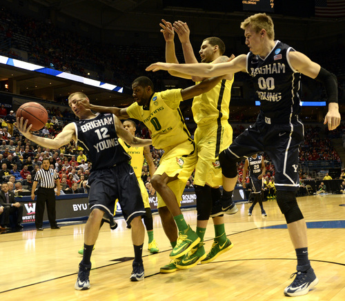 Rick Egan  | The Salt Lake Tribune   Brigham Young Cougars forward Josh Sharp (12) trees to gain control of the ball, as Oregon Ducks forward Mike Moser (0) puts pressure on him, in second round NCAA Championship action, BYU vs. Oregon, in Milwaukee, Thursday, March 20, 2014.