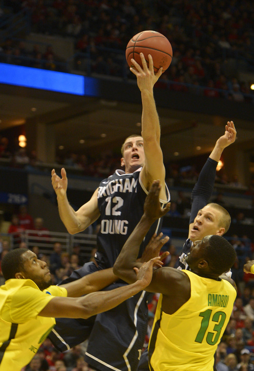 Rick Egan  | The Salt Lake Tribune    Brigham Young Cougars, Josh Sharp (12), goes up for a shot over Oregon Ducks forward Mike Moser (0) Richard Amardi (13), in second round NCAA Championship action, BYU vs. Oregon, in Milwaukee, Thursday, March 20, 2014.  Oregon won the game 87-68.