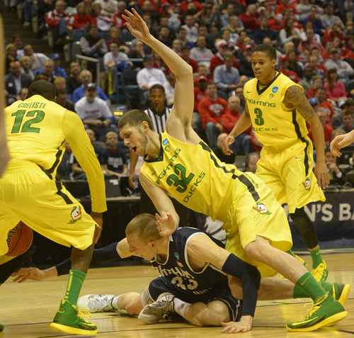 Rick Egan  | The Salt Lake Tribune   Oregon Ducks forward Ben Carter (32) falls on top of Brigham Young Cougars forward Nate Austin (33), in second round NCAA Championship action, BYU vs. Oregon, in Milwaukee, Thursday, March 20, 2014.