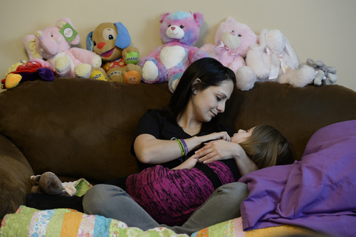 """Francisco Kjolseth     The Salt Lake Tribune Catrina Nelson of West Jordan holds her youngest daughter Charlee, 6, who suffers from Late Infant Batten Disease, a terminal inherited disorder of the nervous system that leads to seizures, loss of vision and motor skills. Surrounded by friends and family, they stay close to Charlee, feeling her spirit at home during hospice care. Gov. Gary Herbert signed """"Charlee's Law"""" after Charlee died last weekend. The law will make cannabis oil available on a trial basis."""