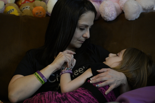 """Francisco Kjolseth     The Salt Lake Tribune Catrina Nelson of West Jordan holds her daughter Charlee, 6, who suffered from Late Infant Batten Disease, a terminal inherited disorder of the nervous system that leads to seizures and loss of vision and motor skills. Her daughter, who was on hospice care at home, was surrounded by friends and family as they comforted one another during her final moments. Gov. Gary Herbert signed """"Charlee's Law"""" after Charlee died last weekend. The law will make cannabis oil available on a trial basis."""