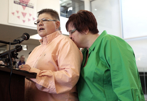Jayne Rowse, left, speaks as April DeBoer, kisses her during a news conference in Ferndale, Mich., Friday, March 21, 2014. A federal judge has struck down Michigan's ban on gay marriage Friday the latest in a series of decisions overturning similar laws across the U.S. The two nurses who've been partners for eight years claimed the ban violated their rights under the U.S. Constitution. (AP Photo/Paul Sancya)