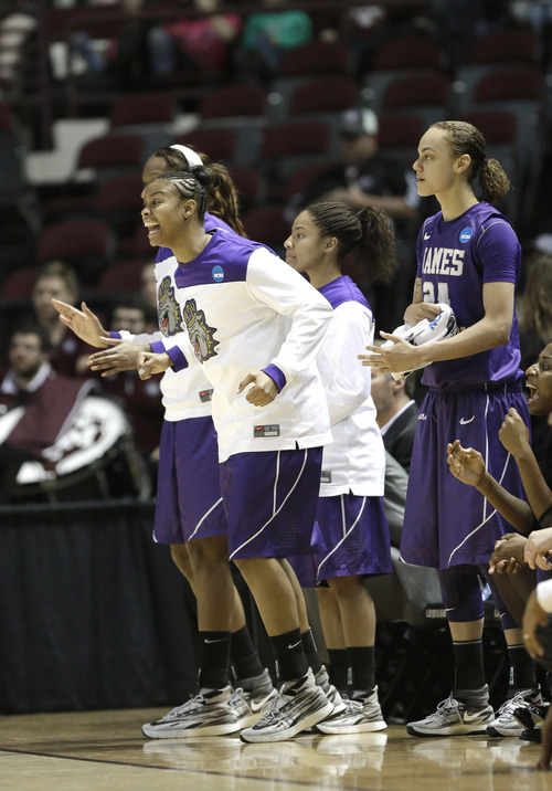 James Madison players celebrate in the final minutes against Gonzaga in the second half of a first-round NCAA women's basketball game Sunday, March 23, 2014, in College Station, Texas. James Madison won 72-63. (AP Photo/Pat Sullivan)