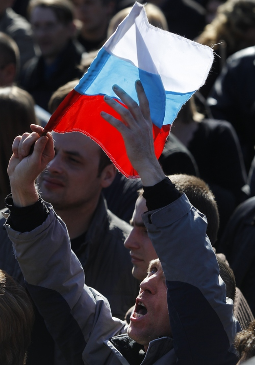 A man holds up his hands as he attends a pro Russian rally at a central square in Donetsk, eastern Ukraine, Sunday, March 23, 2014. About 5,000 people demonstrated in Donetsk in favor of holding a referendum on secession and absorption into Russia. (AP Photo/Sergei Grits)