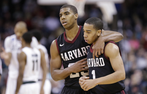 Harvard's Siyani Chambers, right, is comforted by teammate Wesley Saunders late in the second half against Michigan State during the third round of the NCAA men's college basketball tournament in Spokane, Wash., Saturday, March 22, 2014. Michigan State won 80-73. (AP Photo/Elaine Thompson)