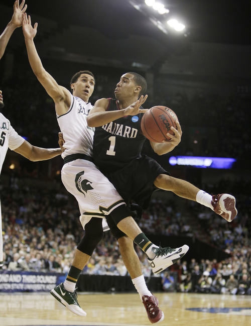 Harvard's Siyani Chambers (1) passes around Michigan State's Travis Trice in the second half during the third-round game of the NCAA men's college basketball tournament in Spokane, Wash., Saturday, March 22, 2014. Michigan State won 80-73. (AP Photo/Young Kwak)