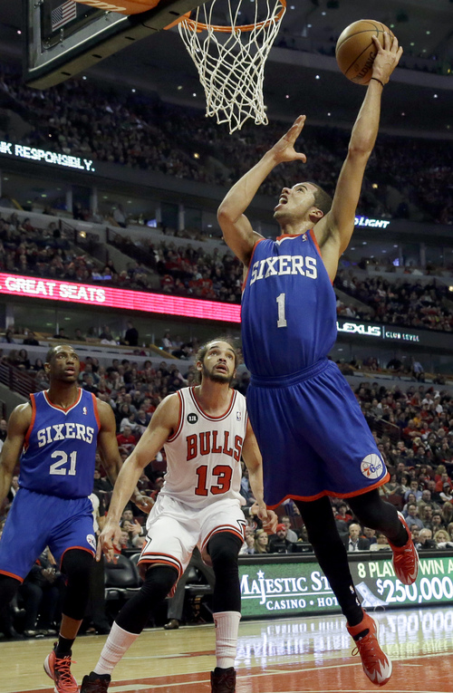 Philadelphia 76ers guard Michael Carter-Williams (1) drives to the basket as Chicago Bulls center Joakim Noah (13) watches during the first half of an NBA basketball game in Chicago on Saturday, March 22, 2014. (AP Photo/Nam Y. Huh)